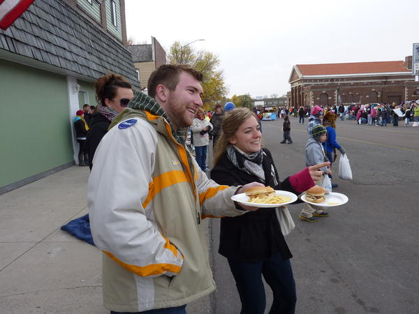 With sandwiches they procured from The Zoo, Anthony Rohr, an NSU student, and alumna Michelle Monroe, of Rock Valley, Iowa, watch the parade. (9:57 a.m.)