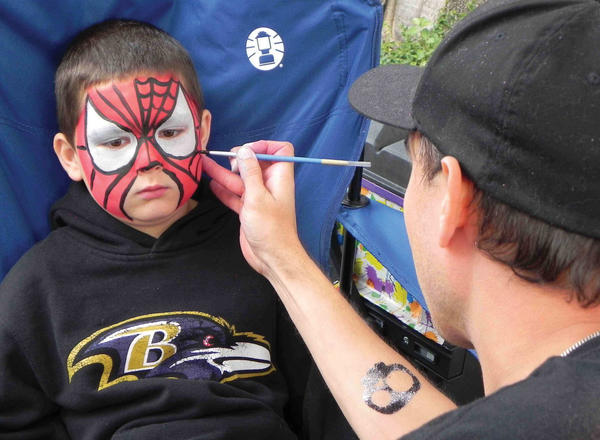 Owen Witmer, 7, of Waynesboro, Pa., didn't move a muscle while Shannon Ross carefully transformed him into a pint-sized Spider-Man on Saturday at the eighth annual Market Day in Waynesboro.