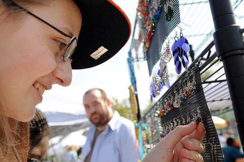 Alina Buechler, a junior at Oakland Mills High, checks out a selection of earrings and other accessories made from chainmail by Baltimore artist Nicholas Thomas, background.