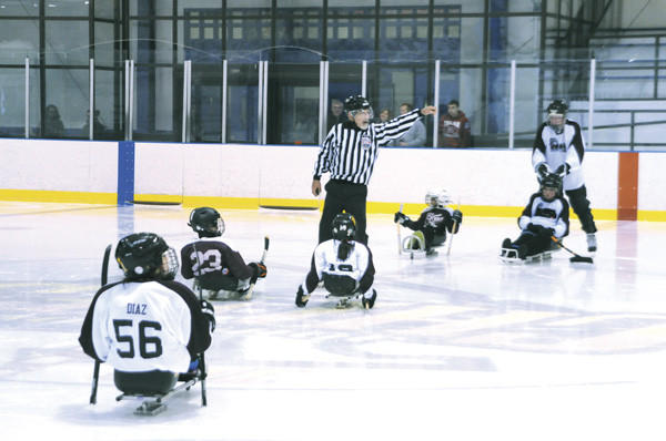 Referee Tom Rizzo signals the start of the Sitting Bulls vs Mighty Otters sled hockey game Saturday.