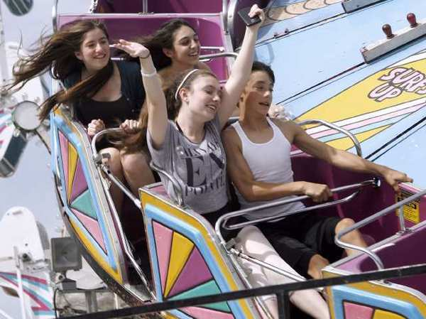 Ana Goodenberger, 16, of La Crescenta, front left, and Miles Parsons, 13 of Montrose, enjoy a ride on The Tidal Wave ride at the Montrose 35th Annual Oktoberfest on Honolulu Ave. in Montrose.