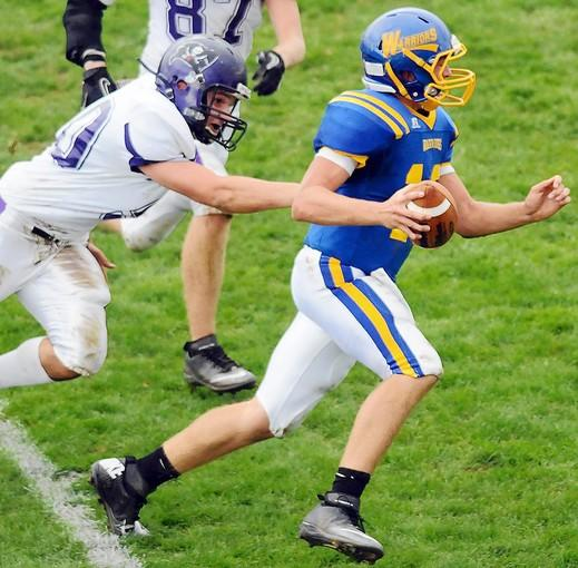 Palisades' Barry Weaver (50) reaches for Wilson's quarterback Ryan Dailey (10) as he runs the ball during their game on Saturday at Wilson Area High School stadium.