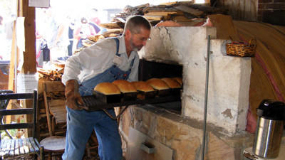Fred Orendorf removes racks of golden brown bread from a kiln, destined to be purchased by the slice by Springs Folk Festival visitors.