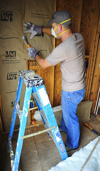 Rob Apgar staples insulation into place Saturday at Habitat for Humanity house on Concord Street. He was part of a work crew from Veritas United Church of Christ in Halfway.