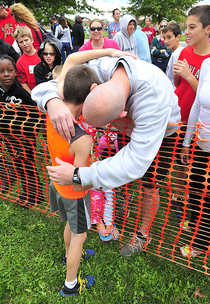 Fourth-grade boys champion Ryan Rasco gets a congratulatory hug from his father, Dean Rasco, on Saturday at Eastern Elementary School.