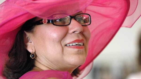 Kenia Gomez, wearing a wide-brim pink hat, reacts to seeing models wearing fashion dresses provided by Dillard's during the Pretty In Pink luncheon and fashion show at the Calexico Cultural Arts Center on Saturday.