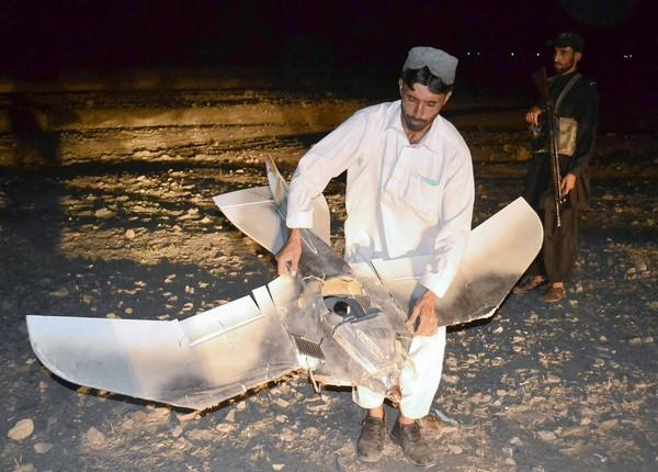 A Pakistani villager holds a wreckage of a suspected surveillance drone that crashed in Pakistan last August.