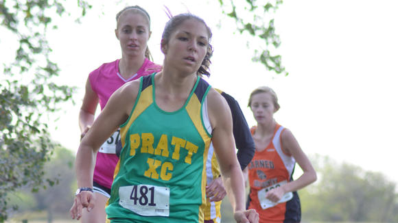 TMP senior Heather Ruder (in pink)stays behind a Pratt runner before eventually winning the meet in Sterling on Thursday.