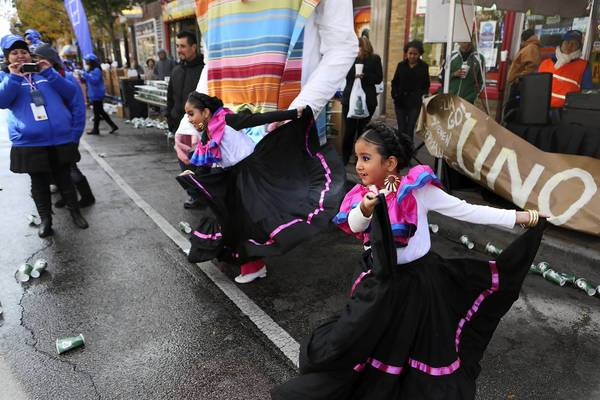Sisters Samantha, 9, left, and Karen Dorado, 6, perform Mexican folk dances for runners making their way through the Pilsen neighborhood during the Chicago Marathon.