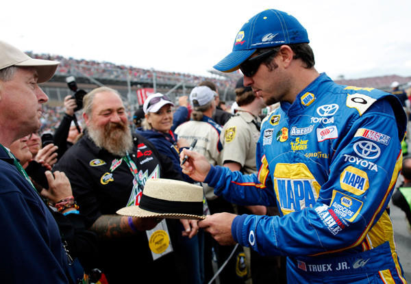 Martin Truex Jr., driver of the #56 NAPA Auto Parts Toyota, signs his autograph for a fan prior to the NASCAR Sprint Cup Series Good Sam Roadside Assistance 500 at Talladega Superspeedway on Oct. 7 in Talladega, Ala.