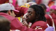 Washington Redskins rookie quarterback Robert Griffin III was knocked out of Sunday's game with a mild concussion, coach Mike Shanahan said.