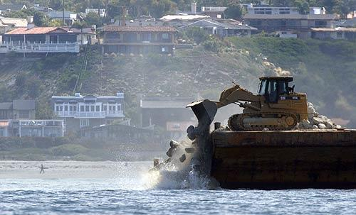 A giant skip loader drops a load of rocks into the waters off San Clemente as part of a reef construction project by Southern California Edison. The reef is a long-planned mitigation measure to protect marine life affected by the San Onofre nuclear plant.