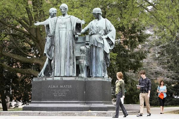 People walk by the Alma Mater statue in March on the University of Illinois at Urbana-Champaign. It has since been moved for a restoration.