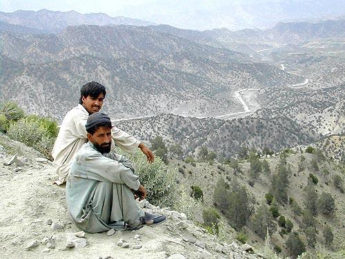 <b>REMOTE TERRAIN:</b> Afghan men sit on a bluff overlooking the road linking Gardez and Khowst. U.S. troops were determined to secure key checkpoints along the road that were used by warlords for extortion. Two detainee deaths linked to a Green Beret unit from Alabama came as a consequence of efforts to pacify the route.