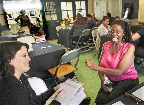 Darlene Williams, right, answers questions from Nichole La May during an interview for a concierge job at the Grove's holiday hiring fair.