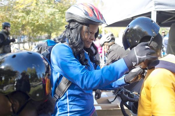 Cynthia Bell fits a child for a bike helmet before a group ride Saturday. The Active Transportation Alliance event celebrated new bike lanes.