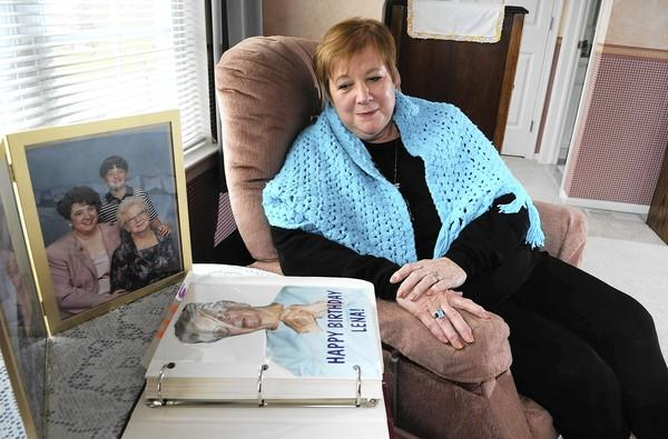 Sylvia Havlish sits in a bedroom in her home filled with her late mother's furniture and wearing a shawl that was her mother's. The shawl brings her comfort in moments of need. At left are photographs of her late mother.