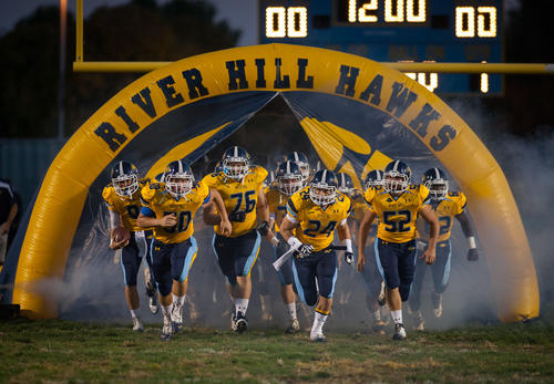 The River Hill Hawks varsity football team runs on to the field before the game against Mt. Hebron.