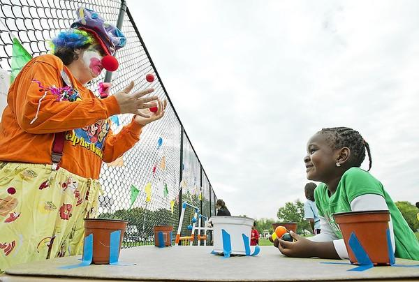 Cheryl Curtis, of Laurel, entertains Amaris Worae, 4, also of Laurel, at a game booth during the Kicks for a Cause fundraiser Oct. 6 at McCullough Field.