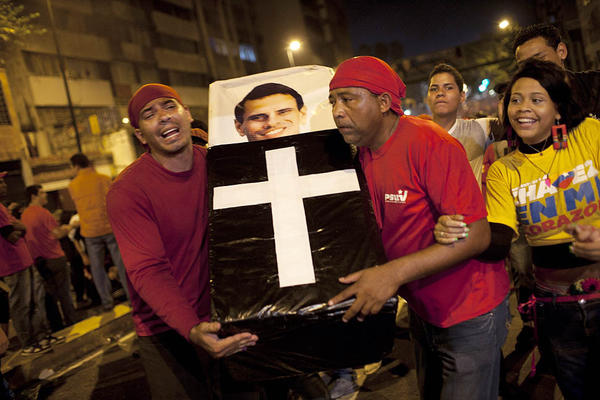 Supporters of Venezuela's President Hugo Chavez perform a mock funeral for opposition candidate Henrique Capriles as they celebrate in downtown Caracas.  Chavez won re-election and a new endorsement of his socialist project Sunday, surviving his closest race yet after a bitter campaign against Capriles.