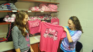 Senior Key Club members Abbey Augustine, left, and Megan Gipe look at the new pink T-shirts the club is selling at the high school to raise money for breast cancer research.