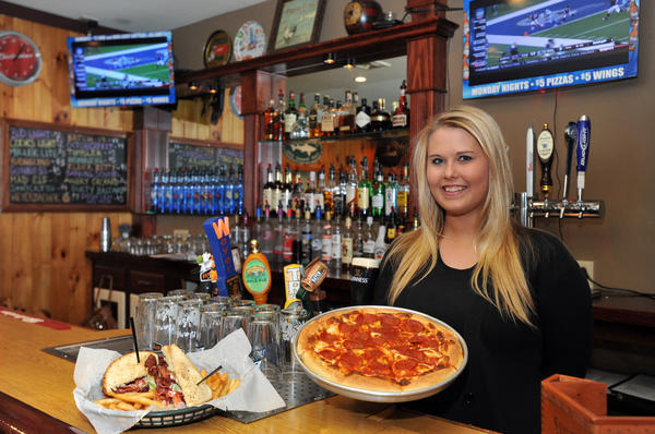 Jenna Smith, bartender at the Pickled Egg restaurant in Wilson holds a mixed pizza with pepperoni made with their garlic sauce and tomato sauce topped with fresh pepperoni. The restaurant is located at 2049 Northampton St., Wilson.