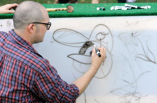Ryan Patterson, organizing artist of Big Draw in the Dell, draws an Oriole bird during the event Saturday, Oct. 6 at Wyman Park in Baltimore.
