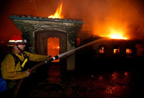 A firefighter sprays water on a burning house in Montecito where more than 100 homes burned during the fast moving Tea Fire.