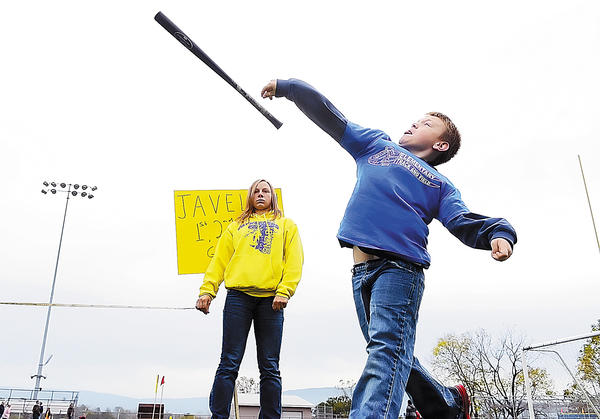 Kaden Ditch, 7, a student at Mowrey Elementary School, competes in the javelin throw Monday during a  track meet for elementary school students in the Waynesboro (Pa.) Area School District. Waynesboro Area Senior High School National Honor Society student Alysha McCleaf prepares to help measure the throw at Indian Stadium in Waynesboro. A whiffle ball bat served as the javelin for the competitors.