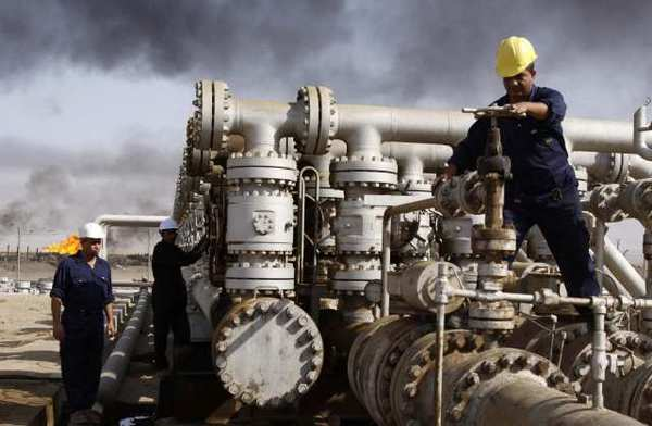 In this 2009 photo, Iraqis work at the Rumaila oil refinery near Basra. The International Energy Agency predicted that Iraq will continue to grow as a global oil power.