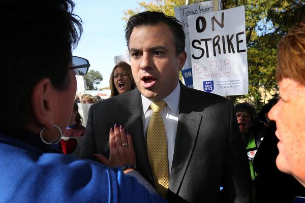 Chicago Federation of Labor President Jorge Ramirez, center, talks with teacher Laura Anzelmo, left, before speaking out on behalf of the Evergreen Park teachers strike at at a rally along the 3500 block of west 95th St. in Evergreen Park.