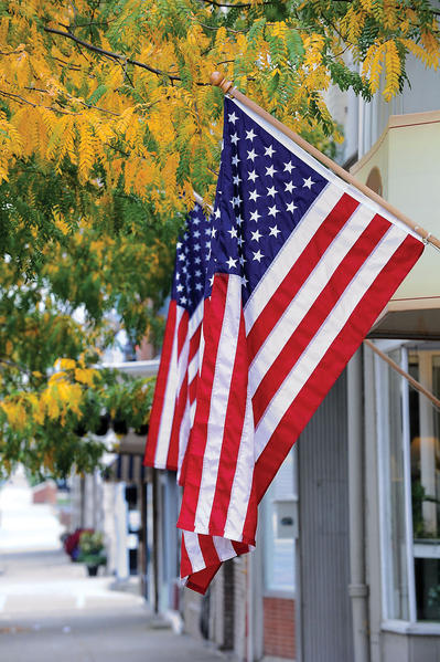Two American flags were intermingled with yellow leaves on South Main Street Monday morning. The flags, and other flags around Winchester, were flying in honor of Columbus Day, the day that Christopher Columbus discovered America on Oct. 12, 1492.