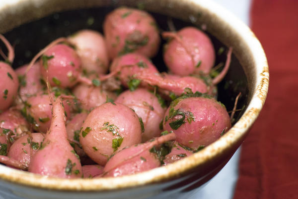 Makes: 8 servings <BR>  5 bunches radishes (35-40)<BR>  1 teaspoon salt<BR>  1/8 teaspoon fresh ground black pepper<BR>  1/4 cup extra virgin olive oil<BR>  1/4 stick butter<BR>  5 sprigs fresh thyme, leaves stripped from the stems<BR>  1/4 cup packed radish greens, minced (optional but tasty)<BR>  Preheat the oven to 375 degrees. In a large non reactive bowl, toss the radishes with the olive oil, salt and pepper. Transfer to a covered baking dish and place into the oven for 50 minutes. Uncover and roast for another 10. The radishes are done when you can put a knife into a radish and pull it out with no resistance. In a small saucepot or pan over medium flame, melt the butter and add the thyme. The butter will begin to bubble vigorously. When the bubbling dies down, cook the butter for another minute and the butter will be ready. It should be hazel in color. Pour the hot butter mixture over the hot radishes, add the radish greens and toss. Serve immediately.<BR>  <b>Tip:</b> You can mash the radishes as a great substitute for potatoes or just as a fun change of pace. If you don't like how wet they become after mashing, you can strain them or cook it off in a hot saucepan.<BR>