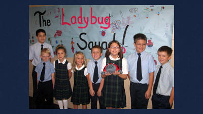 "St. Peter School students show their enthusiasm for their school's participation in Jumpstart's ""Read for the Record"" 2012 campaign which included the book, Ladybug Girl and the Bug Squad. From left are: Adam Brant, Jude Glover, Natalie Riggs, Megan Barron, Caleb Platt, Abby Groholz, Caleb Jano and Ryan Zanoni."