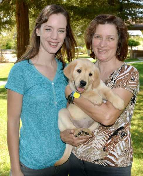 Northwest Glendale Lions new puppy snuggles with its puppy raiser Sarah Jane Chelin and her daughter Chantal Chelin.