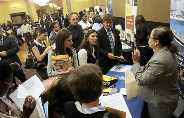 Jobs seekers flood the Caribbean Cruise Line booth at the JobNews Fort Lauderdale job fair at Signature Grand in Davie on in July 2011.