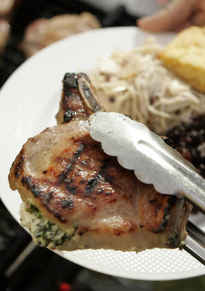 "Stuff thick, center-cut bone-in pork chops with goat cheese flavored with roasted garlic, spinach, and chopped fresh thyme and rosemary up to several hours ahead of time, then grill to order. <a href=""http://www.latimes.com/features/la-fo-tailgaterec28anov28,0,1458056.story"">Click here for the recipe.</a>"