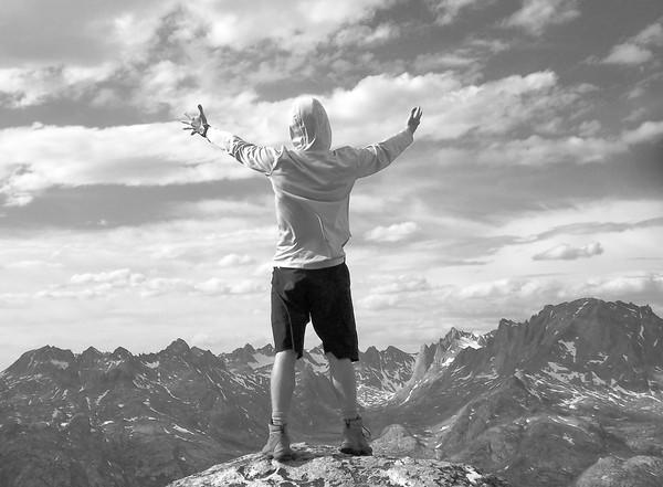 Jake Rigby stands with his hands outstretched on top of a mountain in Glacier National Park in Montana.
