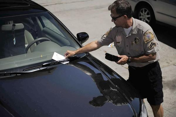An L.A. traffic officer issues a ticket near UCLA; the city recently seized more than $56,000 in parking ticket refund checks that were mailed in 2007 and 2008 but never cashed.