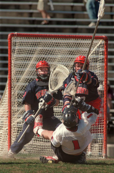 Maryland's Andrew Whipple gets put flat on his back by Virginia as he attempts to take a shot with three seconds left in the second half of a March 28, 1998 game in College Park. Goalkeeper Chris Sanderson, left, and defenseman Penn Leachman guard the net; the Cavaliers were called for a holding penalty on the play. Sanderson and Virginia would go on to reach the NCAA quarterfinals before falling to Syracuse.