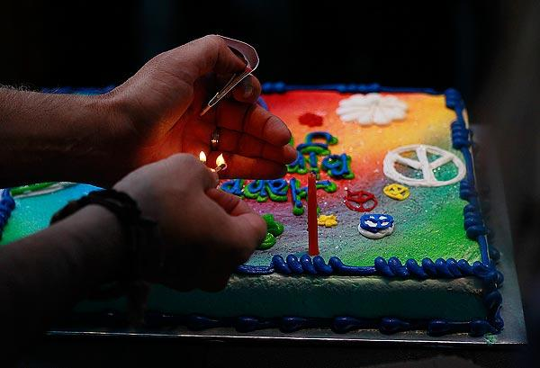 Radio disc jockey Chris Carter lights two candles on a birthday cake as dozens of fans gather outside the Capitol Records building to celebrate John Lennon's 72nd birthday.