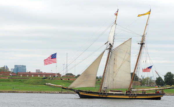 The Pride of Baltimore II participates in the reenactment of the 1814 battle at Fort McHenry . Students watch from the Lady Maryland and other sea vessels.