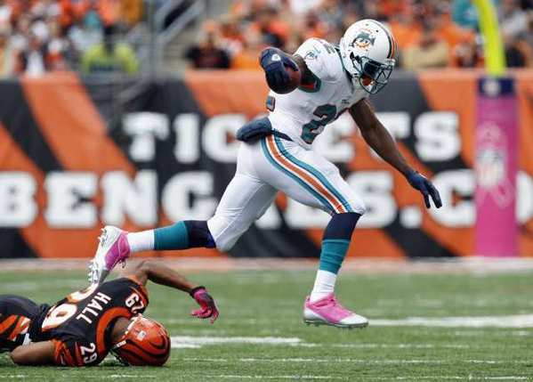 The Miami Dolphins' Reggie Bush runs the ball by the Cincinnati Bengals.