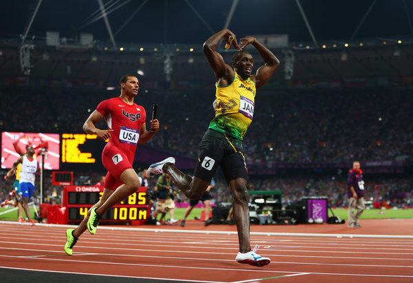Usain Bolt of Jamaica celebrates crossing the finish line ahead of Ryan Bailey of the United States to win gold and set a world record of 36.84 during the men's 400-meter relay final at the London Olympics.
