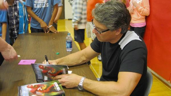 "Monroe Middle School students crowd around author Tim Green as he signs copies of his book, ""Unstoppable."""