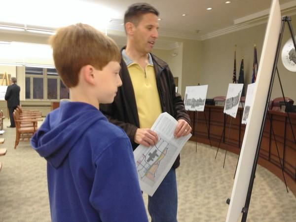 Dan Johnson and his son Colin examine plans of a renovated Charlestowne mall at a recent Open House hosted by the city.