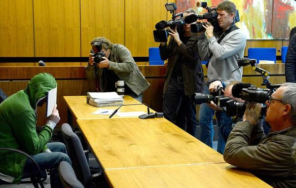 A defendant identified as Andreas S. hides his face from photographers as his murder trial begins in Hildesheim, Germany. The 37-year old father admitted to killing his four children, ages 5, 7, 9 and 12, with a knife as they slept.