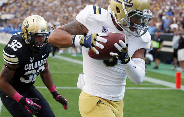 UCLA receiver Darius Bell snags a touchdown pass in front of Colorado linebacker Paul Vigo.