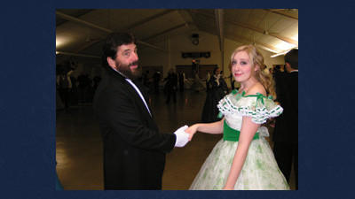 "At the Civil War Gala in 2010, Elena Smith of Pittsburgh wears a stunning ""Gone with the Wind"" dress (like that worn by Scarlett O'Hara in the barbecue scene) for her evening attire, while a caller from the Victorian Dance Ensemble shows his chivalry. Many women sew their dresses for this event every year but Smith rented hers. The 2011 gala was canceled because of weather. Tickets are on sale now for the 5th annual Civil War Gala set for 7:30 p.m. Nov. 3 at Friedens Lutheran Fellowship Hall by calling 814-395-3200."