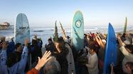 With all the surf culture icons gathered by the Huntington Beach Pier on Sunday morning, it may take the creator of the universe to steal the show.